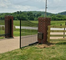Wood split rail fence with arched aluminum estate gate