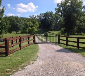 Split rail wood fence with arched aluminum gate